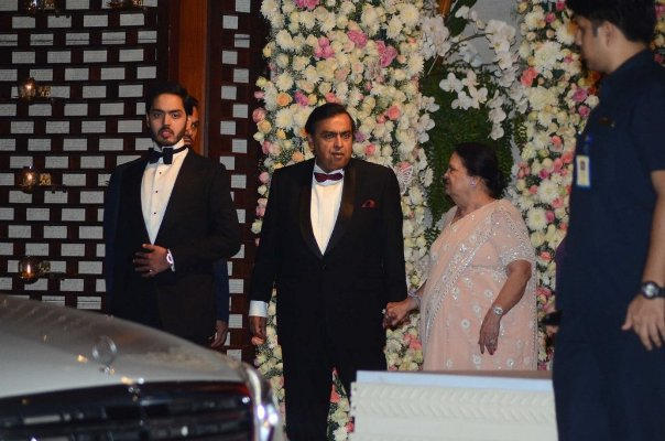 The host of the party, Mukesh Ambani ,Kokilaben Ambani and Anant Ambani standing at the entrance to welcome the guests.