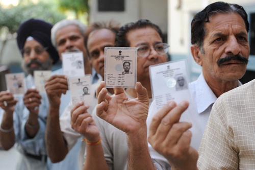 Indian voters hold up their voter ID cards as they stand in a queue to cast their vote at a polling station in Amritsar on May 13, 2009. during the final phase of polling for national elections.  India voters cast their final ballots in the country's marathon elections, with analysts predicting a shaky coalition government that will struggle to survive a full term.