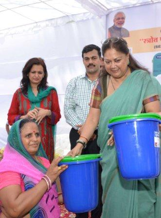 Raje distributing green and blue dustbins to people.