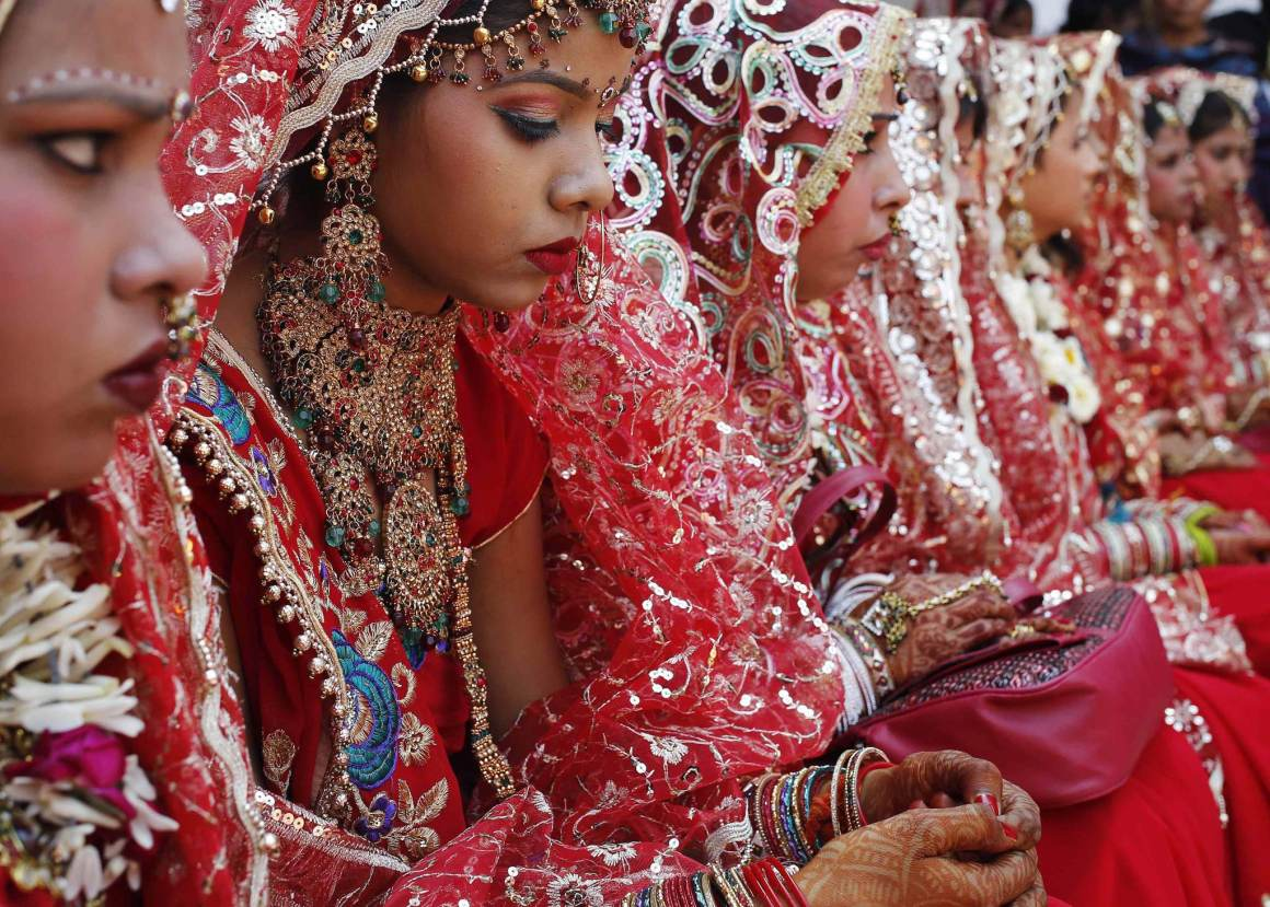 Brides sit as they wait to take their wedding vows during a mass wedding ceremony at a temple in New Delhi